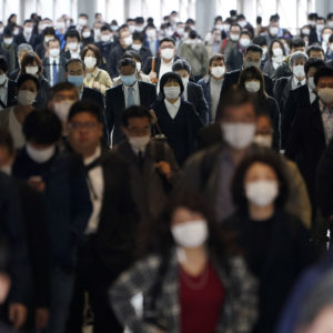 FILE - In this file April 27, 2020 photo, a station passageway is crowded with commuters wearing face mask in Tokyo. Under Japan's coronavirus state of emergency, people have been asked to stay home. Many are not. Many still have to commute to their jobs despite risks of infection, while others continue to dine out, picnic in parks and crowd into grocery stores with scant regard for social distancing. (AP Photo/Eugene Hoshiko, File)